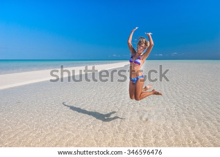 A blonde model in a bikini jumping on a pristine beach with pure white sand - stock photo