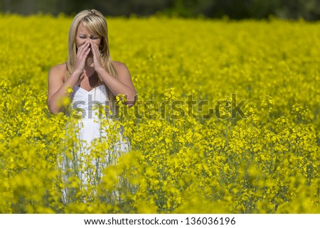 A blonde model in a field of flowers with allergies - stock photo