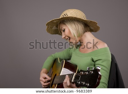 A blonde model in a straw hat and green blouse playing the guitar