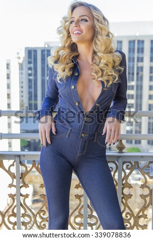 A blonde model posing outdoors on a balcony - stock photo