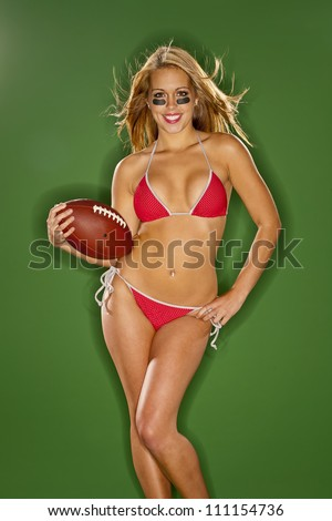 A blonde model posing with a football in a studio environment - stock photo