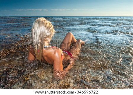 A blonde woman in a bikini relaxing alone in clear water in an idyllic holiday location  - stock photo
