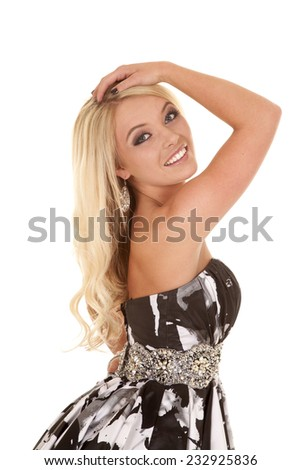 A blonde woman in standing in a black and white dress smiling. - stock photo