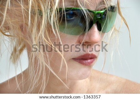 A blonde woman with messy hair, wearing no makeup other than lipstick, hiding behind green sunglasses and looking to the side.  Bad hair day. - stock photo