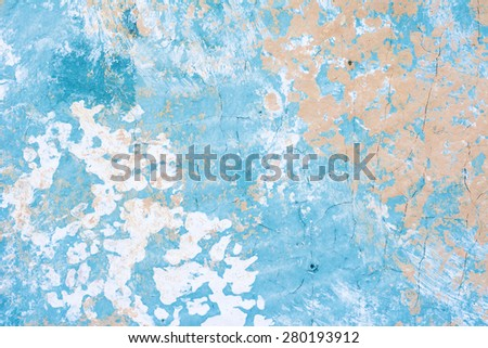 A blotchy, painted wall with cracked, aged areas provide a nice grunge background for placement of copy. - stock photo