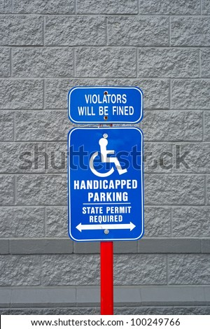 A blue and white handicapped parking sign on a red post with painted wall behind. - stock photo