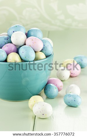 A blue bowl filled with speckled Easter candy eggs. Shallow depth of field. - stock photo