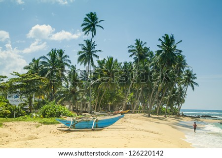 A blue catamaran at the white beach of Hikkaduwa on the beautiful tropical island Sri Lanka. In the background the Indian Ocean with shining turquoise and blue colors and mighty coconut palm trees. - stock photo