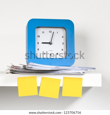 A blue clock placed on a shelf with documents. Sticky notes pasted on the clock. A reminder - concept. - stock photo