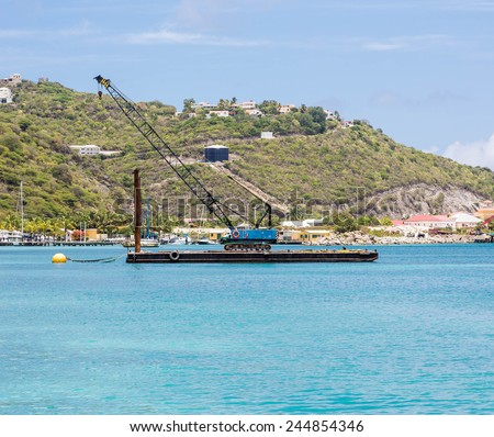 A blue crane on a working barge over blue water in the harbor of Philipsburg in St Martin - stock photo