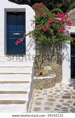 A blue door a some bougainvilleas in an alley of Mykonos island, Greece