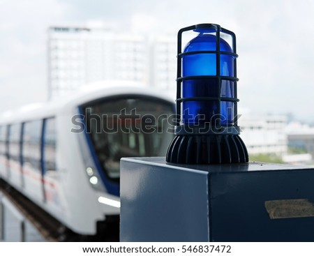 A blue emergency rotating beacon light in a train station.