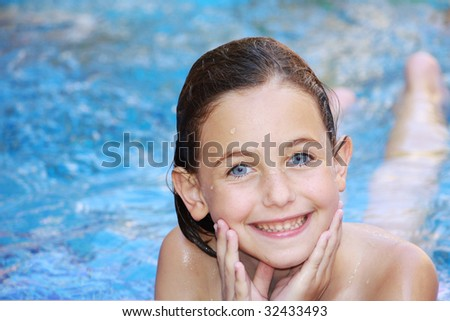 a blue eyed girl lying in a swimming pool smiling at the camera with her hands cupped into her chin - stock photo