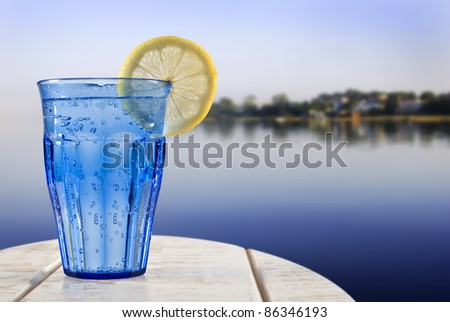 a Blue glass with sparkling water and lemon on a wooden deck overlooking the calm water of a tropical lagune - stock photo