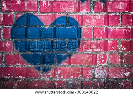 A blue heart, painted with spray can, on a pink wall. - stock photo