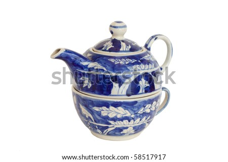 A blue nested ceramic teapot and cup - stock photo