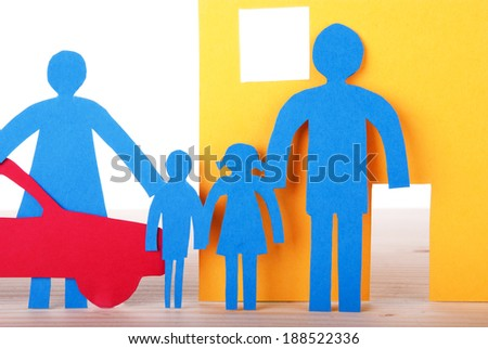 A blue Paper Family in front of their Home with their Car, close-up, isolated - stock photo