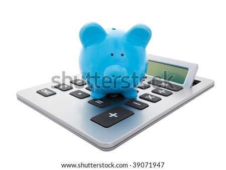 A blue piggy bank sitting on a large calculator.  Conceptual savings.  Isolated with clipping path. - stock photo