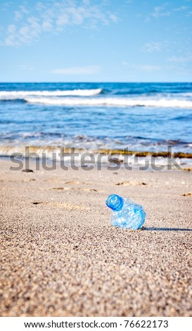 A blue plastic bottle littering a beach - stock photo