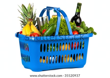 A blue plastic shopping basket on a white background filled with groceries. - stock photo