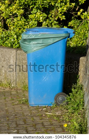 A blue plastic wheely bin with closed lid and green liner placed against a wall with weeds.