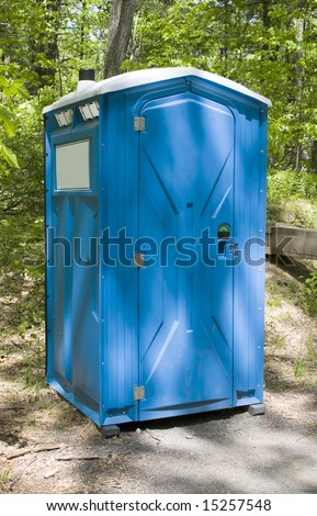 A blue porta potty located on the hiking trail - stock photo