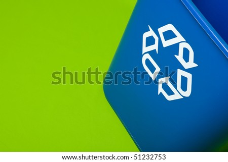 a blue recycle can on a green background - stock photo