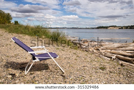 Good A Blue Redoing Lawn Chair On A Rocky Beach Scattered With Weathered Logs