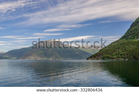 A blue sky with feather clouds over slope of the bank of fjord with beautiful majestic mountains with green forest, Hardangerfjorden, Norway
