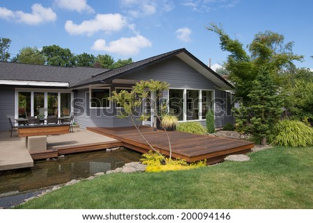 A blue summer sky with white clouds makes the perfect background for this portrait of a contemporary home featuring a deck that spans a water feature emulating a rock lined stream. - stock photo