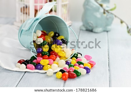 A blue tin bucket tipped over, spilling jelly beans onto a table. Shallow depth of field.