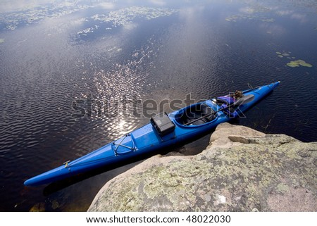 A blue touring kayak sits beside a rock on a lake - stock photo