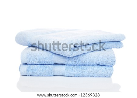 A blue towels stacked reflected on white background - stock photo