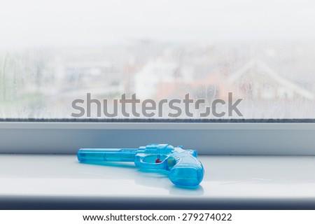 A blue toy gun on a window sill - stock photo