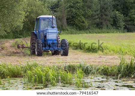 a blue tractor fitted with hay turning equipment in a traditional water meadow with reeds and water lillies in the foreground and trees behind