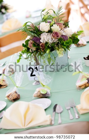 a blue wedding table with cookie favors and flower centerpiece - stock photo