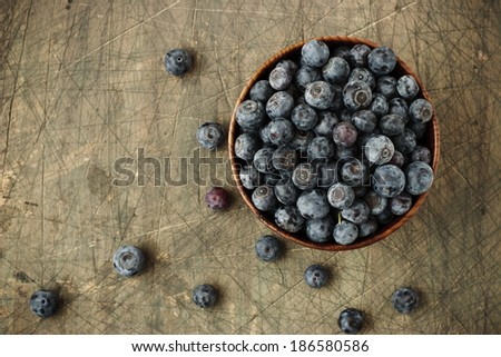 A blueberries in the wooden dish on the wooden board