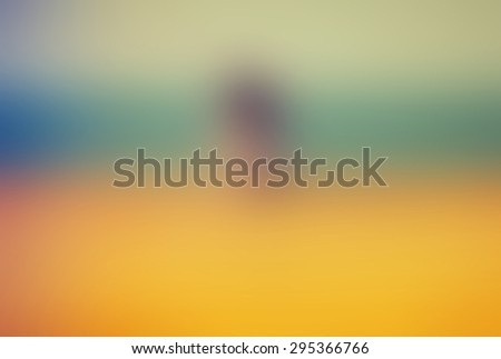 A blurred background of a girl sitting by the beach, with vibrant colors surrounding her - turquoise and yellow. Sky and sand. - stock photo