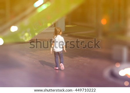 A blurred picture of little girl walking alone in shopping area, filtered color tone - stock photo