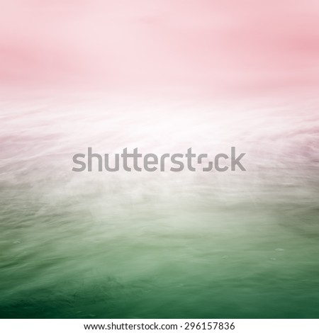 A blurred time exposure of ocean water movement with a glowing center and overlaid with a green to pink color gradient. - stock photo