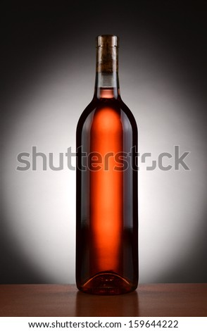 A blush wine bottle backlit with a light to dark spot background. Vertical format.  - stock photo