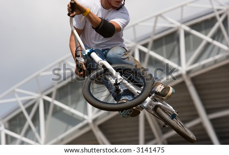 A BMX (Bicycle Moto-cross(X)) in the air against an industrial background
