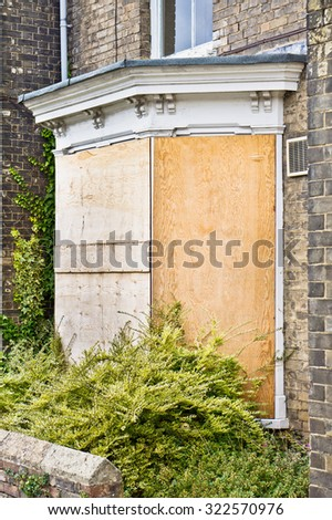 A boarded up blue front door - stock photo