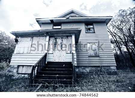 A boarded up, broken down, abandoned, haunted house in cold, blue tones.