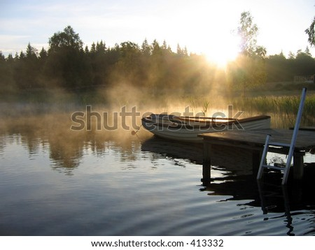 A boat at a bridge at sunrise.
