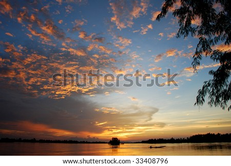 A boat crossing the Mekong River at sunset. Four thousand islands in Laos in the rainy season. - stock photo