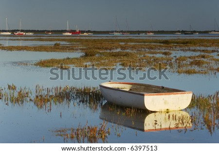 A Boat floating on the Burnham Deepdale marshes at high tide - stock photo