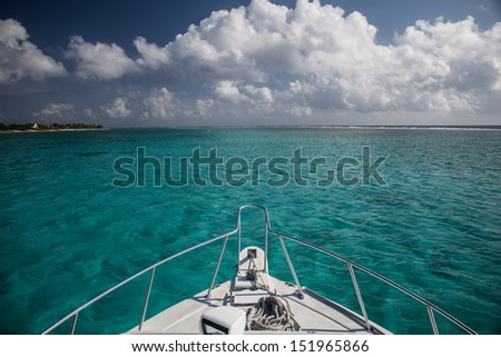 A boat heads across the aqua waters of Grand Cayman's eastern lagoon.  The islands of the Caribbean are popular destinations for tourists. - stock photo