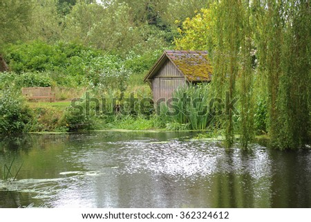 A Boat House on the River Sow with an Overhanging Weeping Willow Tree (Salix babylonica) near the Rural Village of Milford in Staffordshire, England, UK