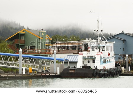 A boat in the harbor of a small town in Alaska.  There are colorful buildings in the background, and pine trees surrounded by mist and fog. - stock photo